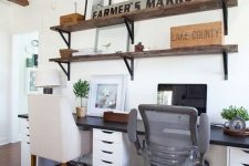 a modern farmhouse home office with an open shelving unit, a shared desk with a black countertop, some chairs and wooden beams