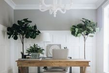 a modern home office with a white chandelier, a wooden trestle desk, a white chair, a printed rug and statement plants