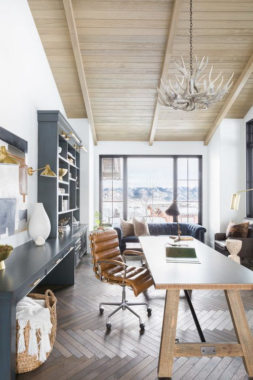 a modern rustic home office with a large graphite grey storage unit, a wooden desk, a leather chair and an antler chandelier