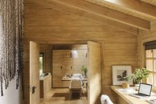 a modern rustic home office with a shared desk, a couple of chairs, an attic ceiling with a skylight and soem faux fur