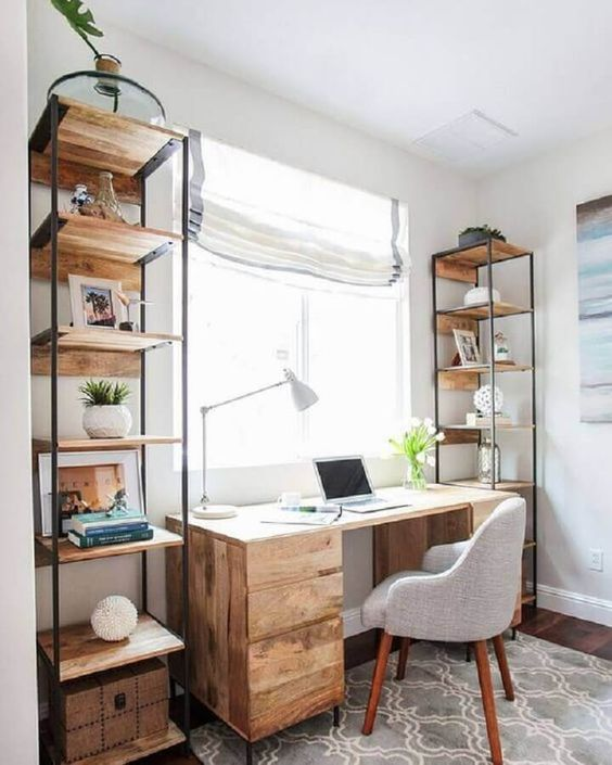 a modern rustic home office with a wooden desk and open shelving units, a printed rug, a grey chair and Roman shades