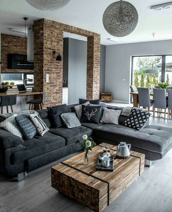 a modern rustic living room with a wood slab table and brick walls and a brick arch is veyr stylish