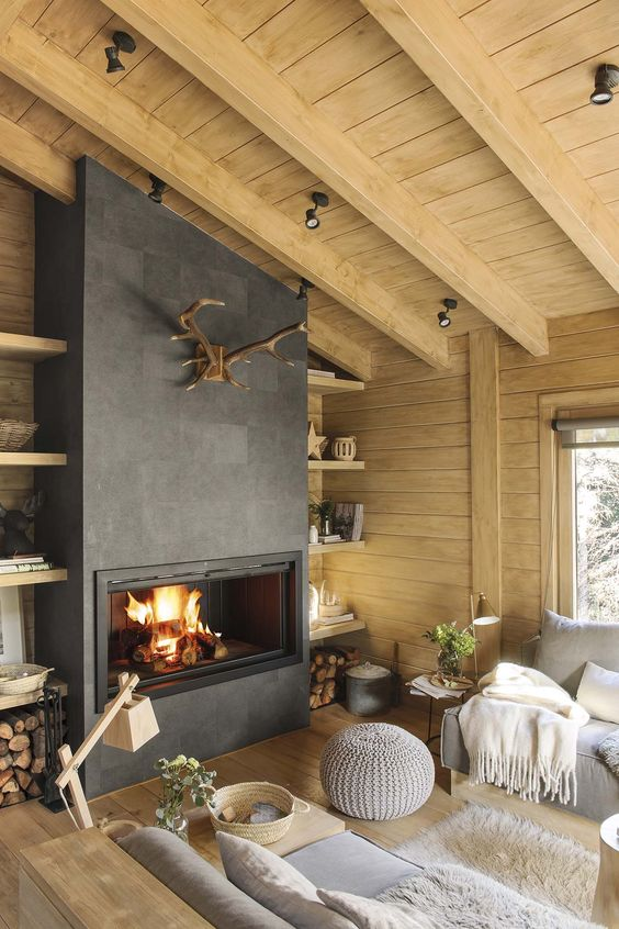 a modern rustic living room with wooden walls and a ceiling, a fireplace, firewood stored by it and antlers