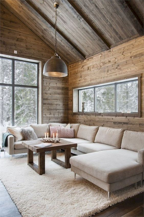 a modern rustic living room with wooden walls and floors, simple neutral furniture and a pendant lamp