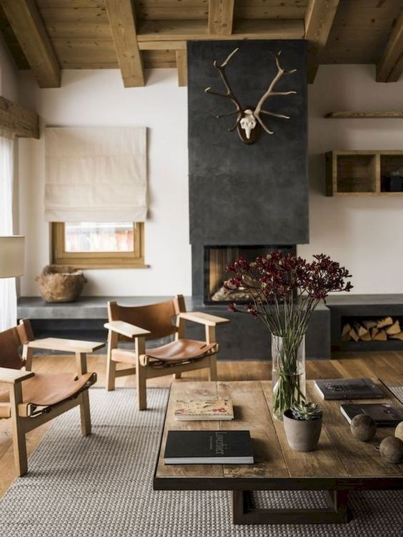 a modern rustic space with a built-in fireplace and firewood storage, a jute rug, sleek wooden furniture with leather