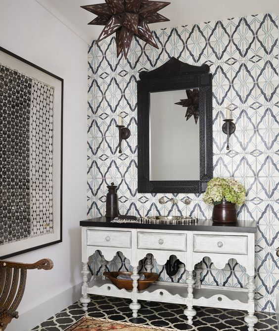 a monochromatic Moroccan bathroom with catchy tiles on the wall and floor and a carved vanity