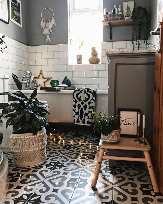a monochromatic boho bathroom with mosaic tiles, subway white one,s a drema catcher, potted plants, lights and a tub