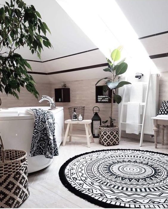 a monochromatic boho bathroom with printed textiles and patterned baskets, plants, a tub and lanterns