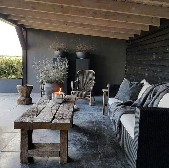 a moody rustic patio with wooden beams on the ceiling, wicker and wooden furniture, potted greenery and minimalist pillows