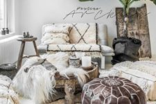 a neutral Moroccan living room with lots of patterned textiles, a leather ottoman and a potted palm