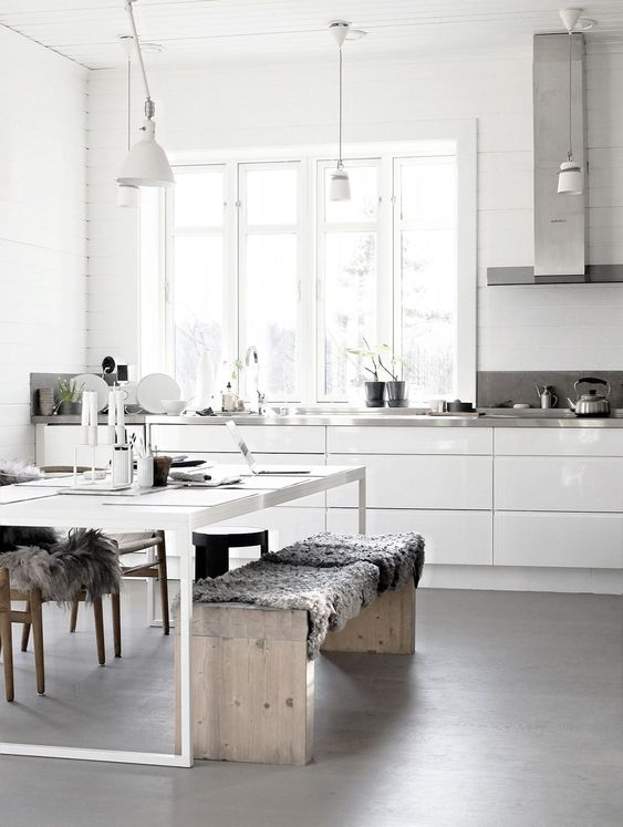 a neutral Nordic kitchen with sleke white cabinets, metal countertops, a white table and wooden benches plus pendant lamps