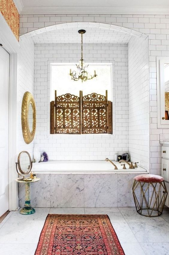 a neutral bathroom with a Moroccan feel, a gilded mirror, a boho rug, a beautiful screen on the window and a geometric stool