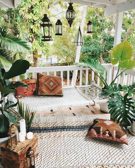 a neutral boho patio with a woven hammock, printed rugs, pillows, candles and lanterns hanging over the space