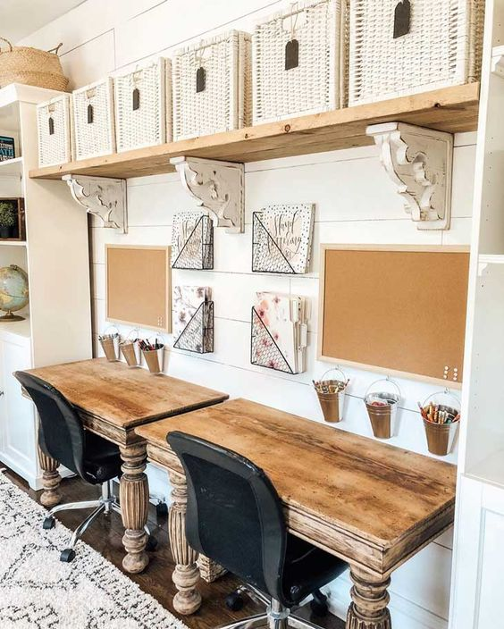 a neutral farmhouse home office with a shelf with white baskets, two matching desks and black chairs and some stuff on the wall