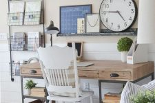 a neutral farmhouse home office with a wooden desk, open shelving, a vintage white chair and a ledge