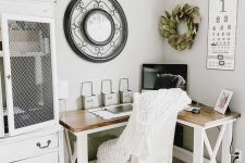 a neutral farmhouse with a corner desk, a white chair, a large cabinet, some greenery and a large clock