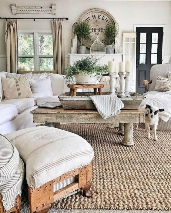a neutral rustic living room with rough wooden tables, a stool, some whitewashed candleholders and a jute rug