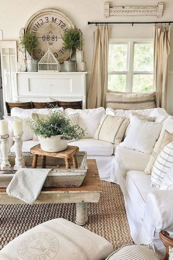 a neutral rustic living room with wooden tables, whitewashed wood elements and white and neutral furniture for a farmhouse feel