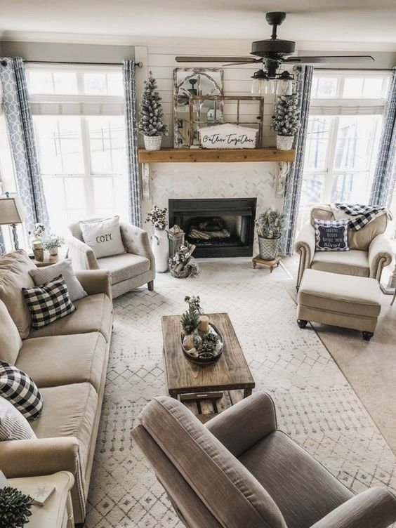 a neutral rustic living space with a woode table and mantel, some touches of buffalo check and flocked mini Christmas trees