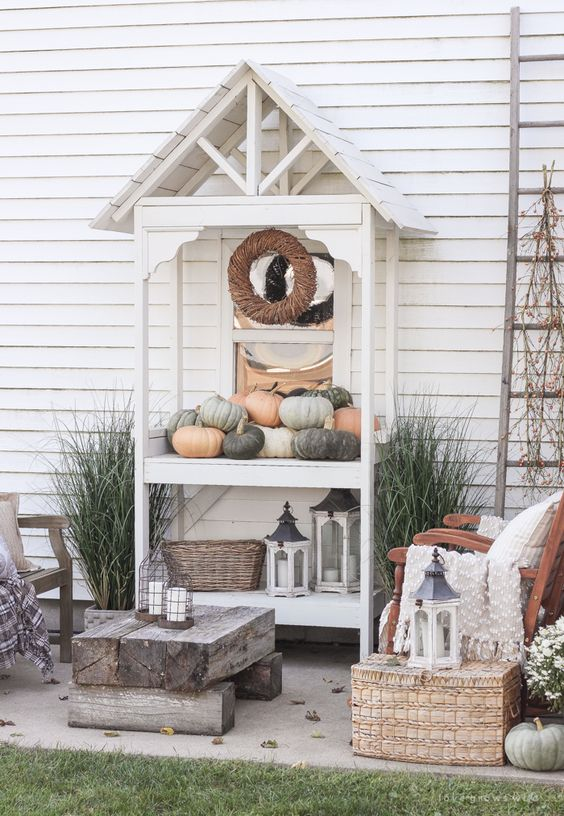 a neutral rustic patio with wooden chairs, a log table and a wicker chest plus a console with pumpkins