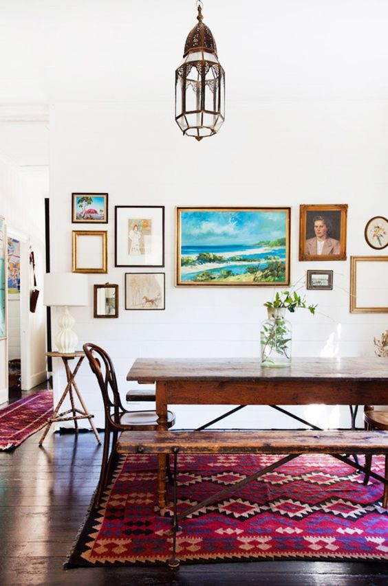 a pretty dining space with a wooden table, chairs and a bench, a bright gallery wall, a Moroccan lamp and a bright rug on the floor