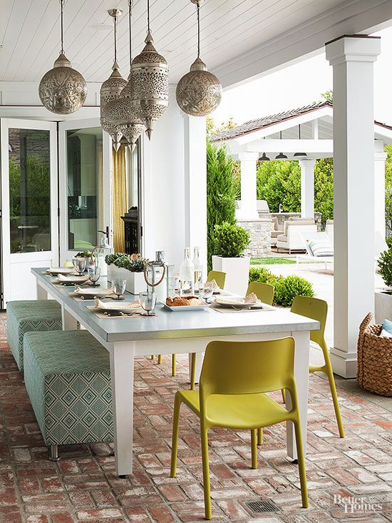 a pretty outdoor dining space with beautiful Moroccan pendant lamps, a long table with printed poufs and bright chairs