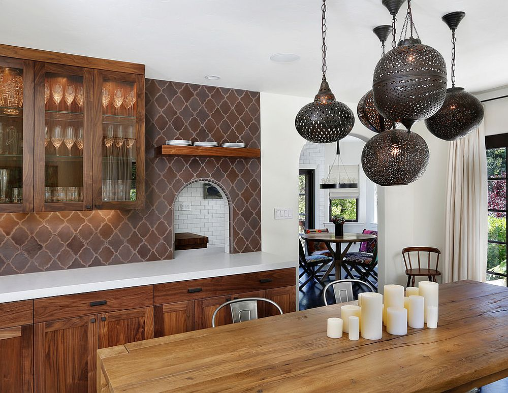 a refined eat-in kitchen with dark stained cabinets, a brown Moroccan tile backsplash, a wooden table and metal pendant lamps over it