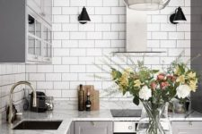 a retro-inspired Nordic kitchen with white tiles, stone countertops, grey cabinets and pendant lamps