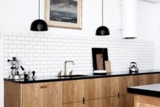 a retro-inspired Scandinavian kitchen with light wood cabinets, black countertops, black pendant lamps, a white tile backsplash