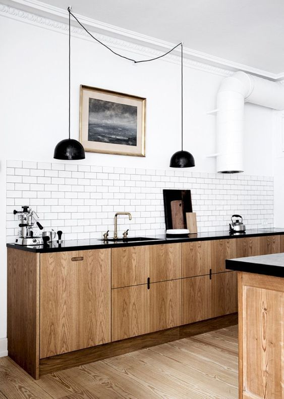 a retro-inspired Scandinavian kitchen with light wood cabinets, black countertops, black pendant lamps, a white tile backsplash