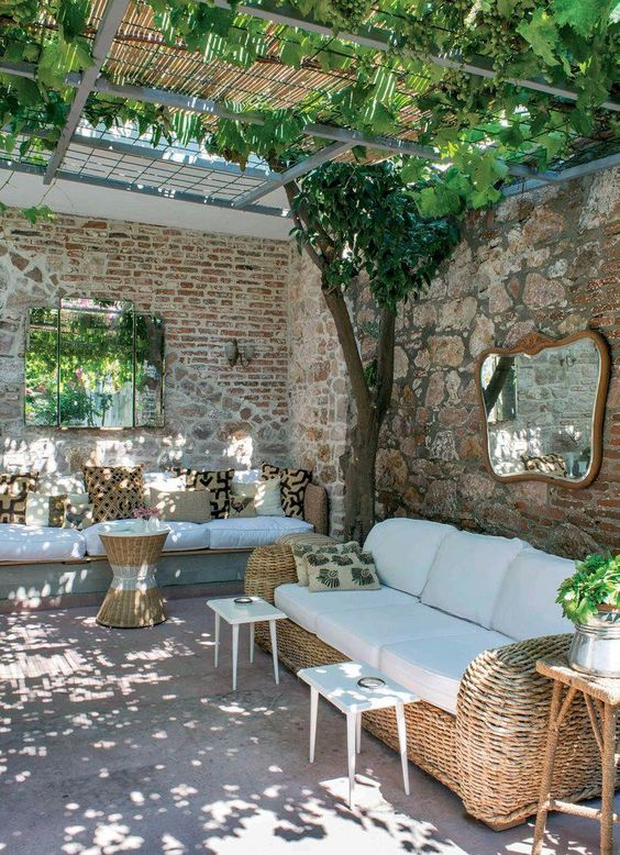 a rustic Spanish terrace with wicker furniture and printed pillows, white tables and greenery and trees