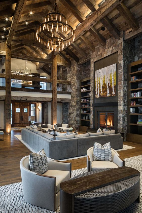 a rustic cabin living room with a wooden ceiling with beams, a stone fireplace and a wall, a large chandelier and neutral furniture