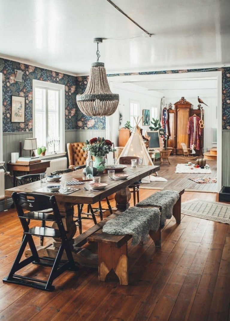 a rustic dining space with a Moroccan feel, a wooden table, benches and chairs, a leather chair and floral wallpaper