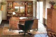a rustic home office with a rough wooden ceiling, heavy wooden furniture, a vintage rug, a leather chair and some lamps