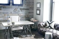 a rustic home office with a salvaged wood wall, a vintage chandelier, a faux fur rug, a trestle desk, a white chair and a leather sofa