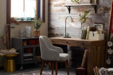 a rustic home office with a salvaged wooden wall, a wooden desk and a metal cabinet, some open shleves and a striped chair