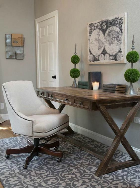 a rustic home office with a trestle desk, a printed rug, green topiaries, a white chair on casters is elegant