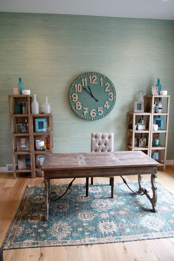 a rustic home office with a wooden desk and shelves, a clock, a bold rug and some decor
