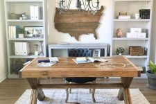a rustic home office with open storage units, a wooden trestle desk, a printed rug and a state artwork on the wall