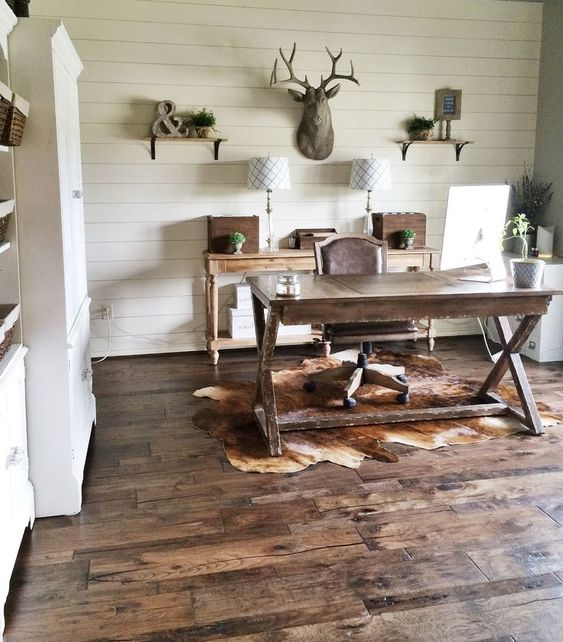 a rustic home office with shelves, a wooden console, table lamps, a wooden trestle desk, a leather chair and a deer head