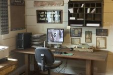 a rustic industrial home office with beadboards, a wooden desk, a shabby cabinet, a modern chair and a bucket