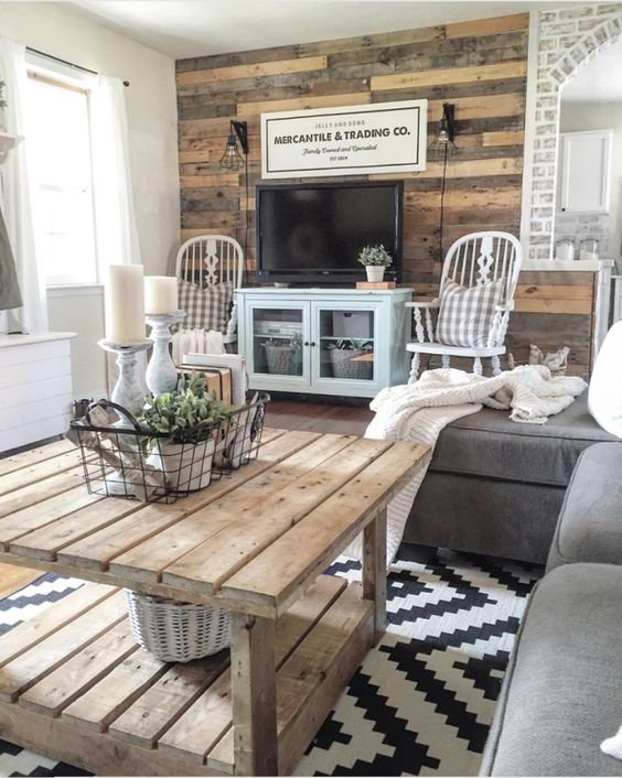 a rustic living room with a reclaimed wood wall, a wooden table, grey and blue furniture and refined vintage chairs