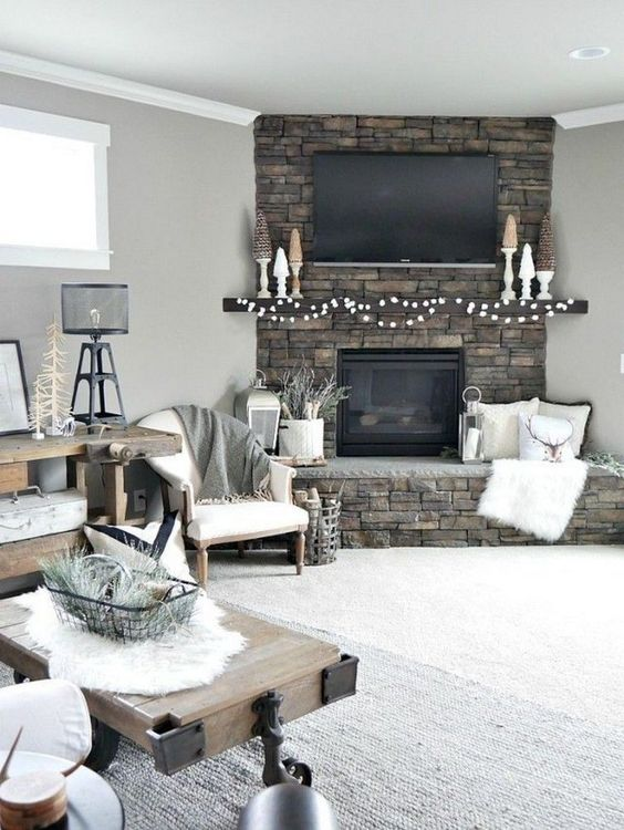 a rustic living room with a stone clad fireplace, a wooden console and a coffee tble plus mini trees