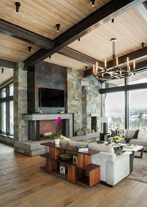 a rustic living room with a stone clad fireplace, dark metal and cocnrete, a wooden ceiling with beams and a wooden storage unit