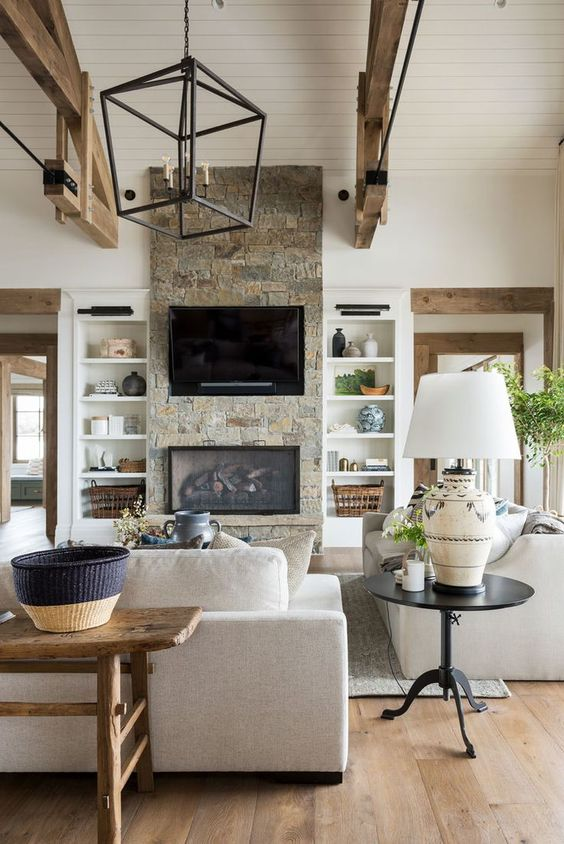 a rustic living room with wooden beams, a stone clad fireplace and some wooden furniture looks very cozy and welcoming