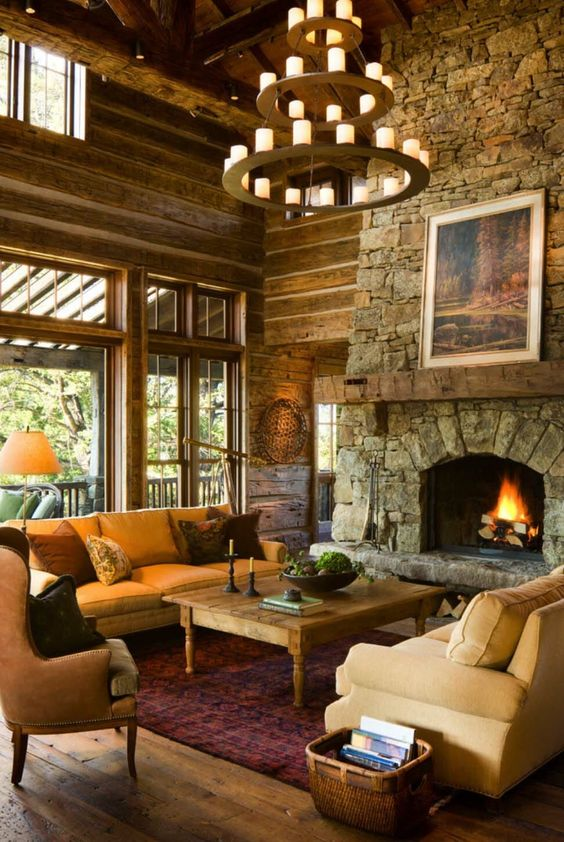 a rustic mountain living room with a stone clad fireplace, a large candle chandelier, cozy furniture and wooden walls