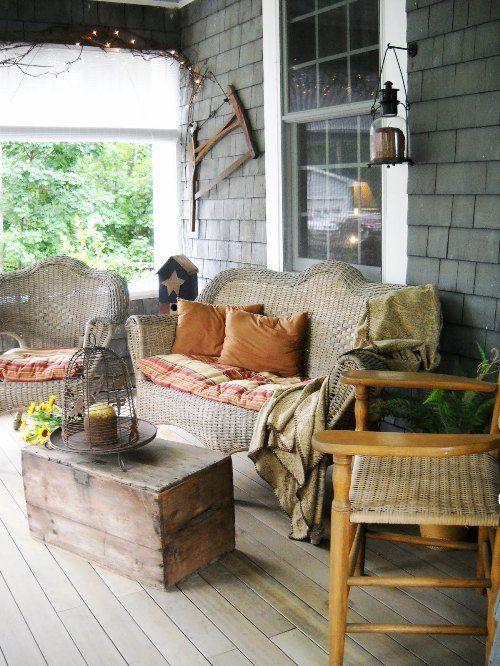 a rustic patio with wicker and wooden furniture, lanterns, a cage candle lantern and striped textiles
