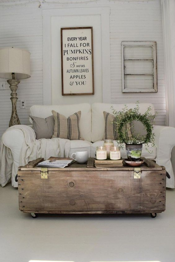 a rustic sitting room with whitewashed shutter walls, neutral furniture and a large stained coffee table
