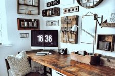 a rustic vintage home office with a shared desk, some art on the wall, wooden chairs and lots of rustic decor