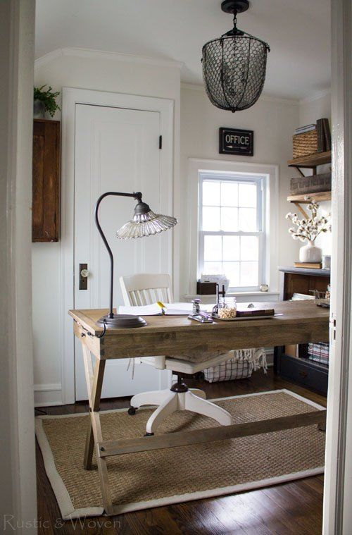 a rustic vintage home office with a wooden trestle desk, vintage lamps, a white chair and cotton branches in a vase
